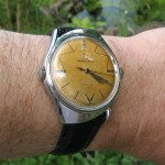 Swisselectric watch being worn and clearly showing the two crowns.